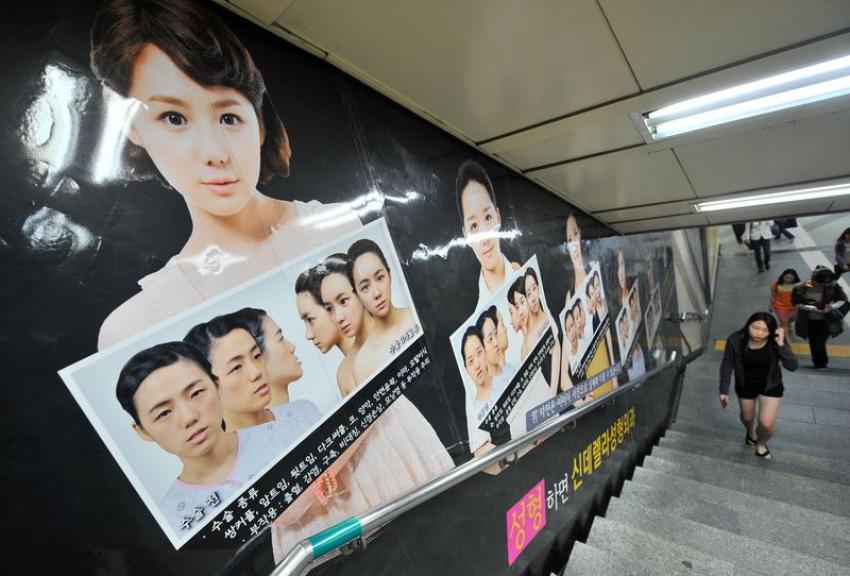 1331797-une-affiche-publicitaire-pour-la-chirurgie-orthgnatique-dans-une-station-de-metro-a-seoul-en-coree-du-sud-le-22-mai-2013